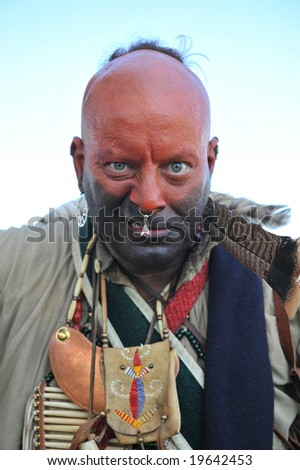 Angry looking warrior dressed in war paint and wearing jewelry - stock photo