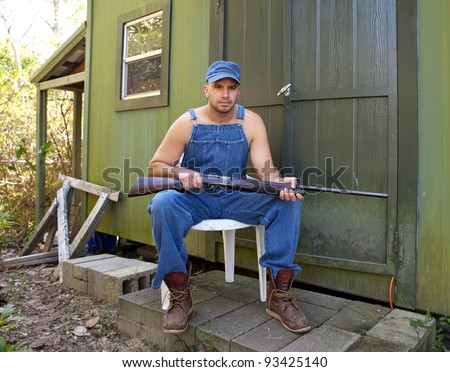 Angry looking young man in old overalls, seated and holding a shotgun outside a cabin or hunting camp. - stock photo