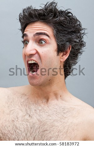 Angry looking young man screaming - stock photo