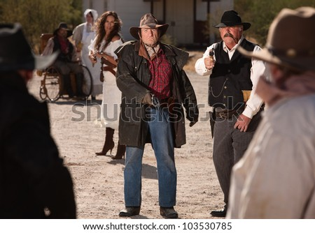 Angry male and female gunfighters pull out their weapons - stock photo