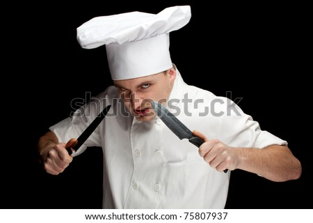 angry male cook in white uniform and hat with two knifes, black bckground
