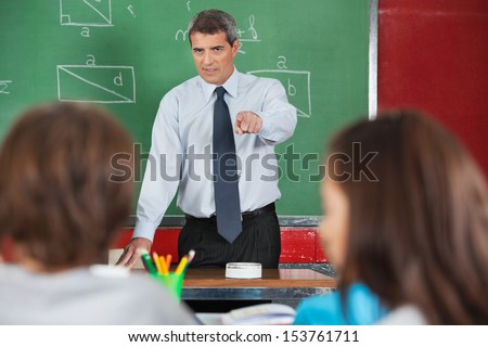 Angry male teacher pointing at students in classroom - stock photo