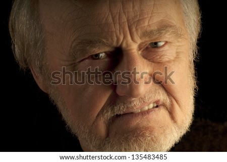 Angry man, a close up portrait of a male senior citizen. - stock photo
