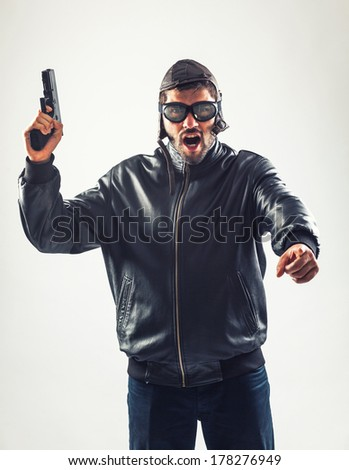 Angry man disguised as a pilot is holding a gun pointed upwards and is threatening - isolated on white