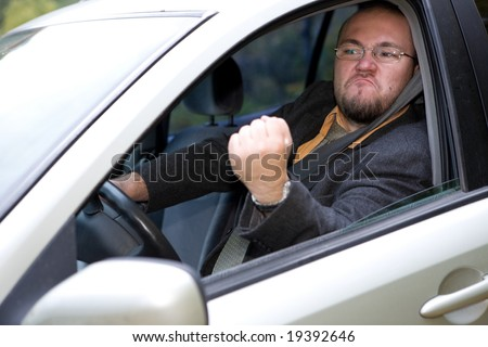angry man driving by car - stock photo