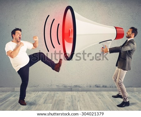 Angry man fights to a big megaphone - stock photo