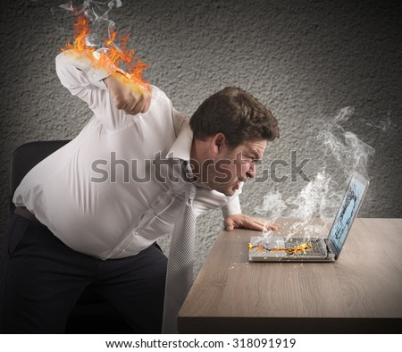 Angry man gives fiery fist to computer - stock photo