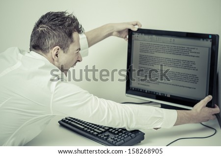 angry man grabbing his computer  - stock photo