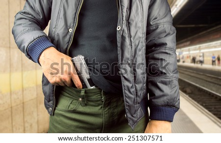 Angry man holding gun against in the subway - stock photo
