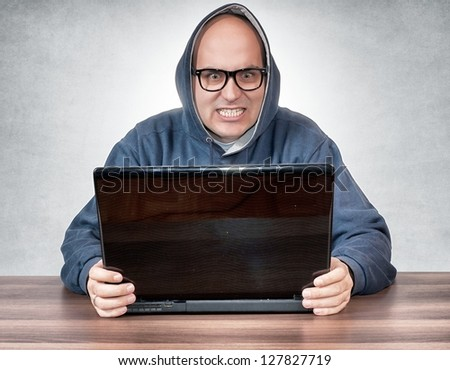 Angry man holding the lap top - stock photo