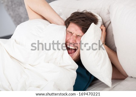 Angry man in bed awoken by a noise - stock photo