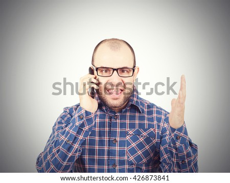 Angry man in glasses yells into  phone. Isolated on white background. - stock photo