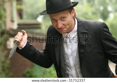 angry Man in hat holding hunting knife