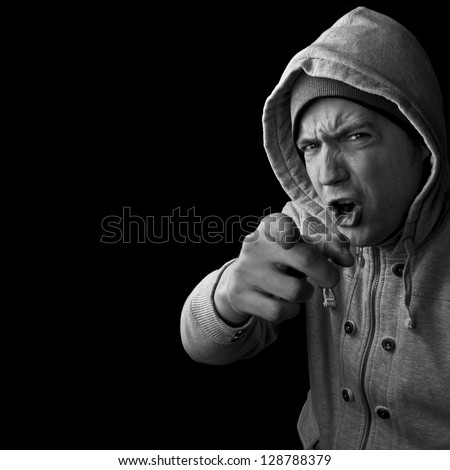 angry man in hoodie pointing his finger and shouting at you - stock photo