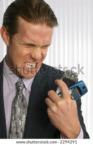 Angry man in suit with smashed cellphone in hand. - stock photo