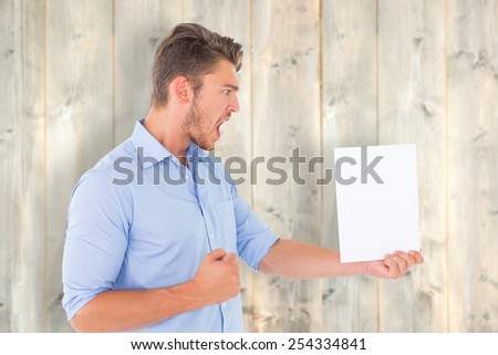 Angry man looking at page against pale wooden planks - stock photo