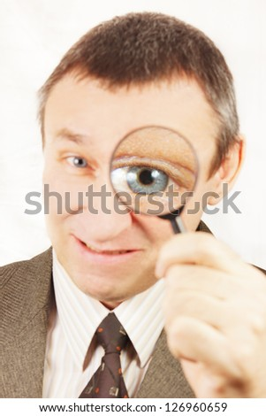 Angry man looks through a magnifying glass - stock photo