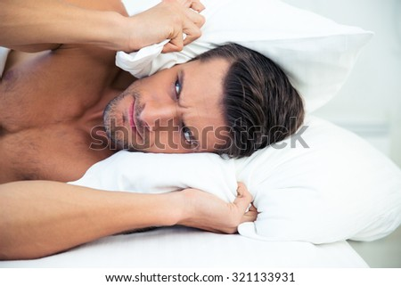 Angry man lying in the bed with pillow on head at home - stock photo