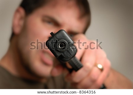 Angry man pointing gun at camera. Shallow depth of field with focus on gun barrel.