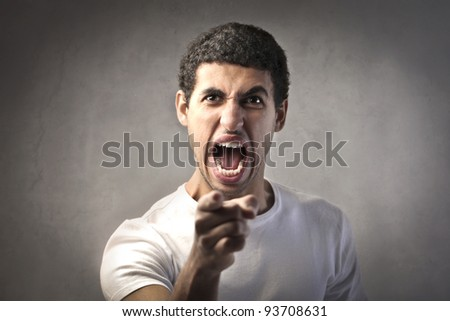 Angry man pointing his finger at someone - stock photo