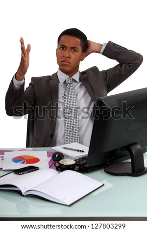 Angry man sat at desk with graphs - stock photo