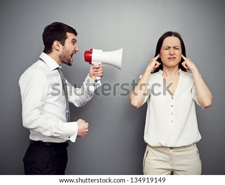 angry man screaming in megaphone at the woman. studio shot over dark background - stock photo