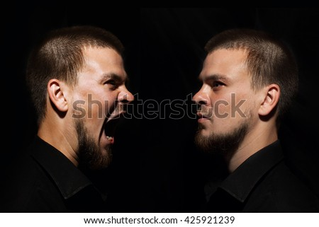 Angry man screaming. Terrible nasty man. A man in a black shirt. Male emotional portrait.   - stock photo