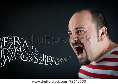 Angry man shouting against black background with letters coming out from his mouth. Conceptual image. - stock photo