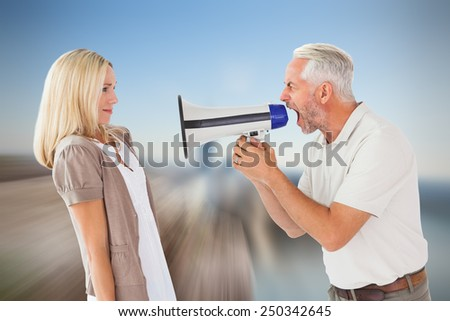 Angry man shouting at girlfriend through megaphone against large rock overlooking foggy city - stock photo
