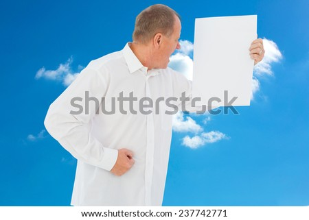 Angry man shouting at piece of paper against cloudy sky - stock photo