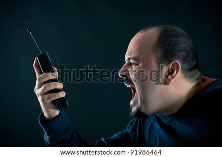 Angry man shouting at the phone against black background.