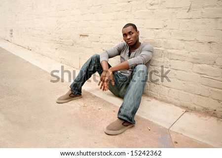 Angry Man Sitting in an Alley Way - stock photo