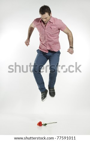 angry man stomping on flower - stock photo