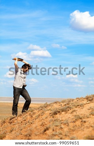 angry man throwing laptop outdoors - stock photo