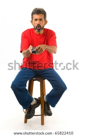 Angry man trying to use the remote control . - stock photo