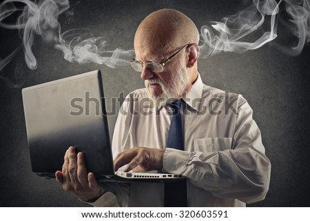 Angry man using a laptop - stock photo