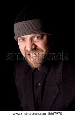 Angry Man wearing a knit hat over a black background - stock photo