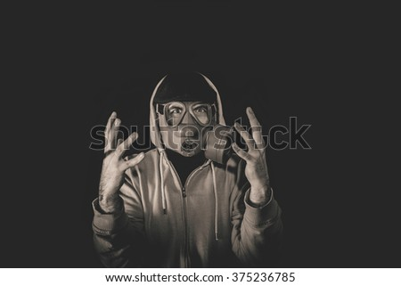 Angry man wearing gas mask,low key and monochrome - stock photo