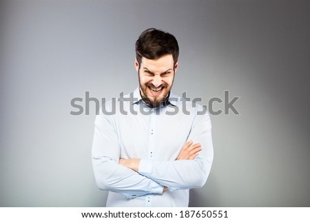 angry man with hands folded on grey background