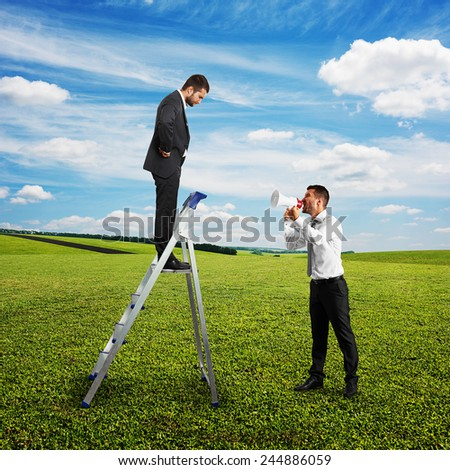 angry man with megaphone screaming at man on the stepladder at outdoor - stock photo