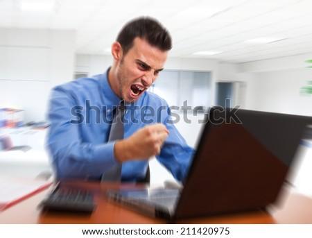 Angry man yelling at his computer - stock photo