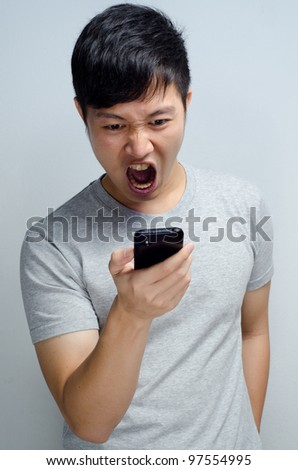 angry man yelling to his mobile phone - stock photo