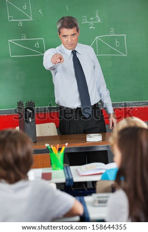 Angry mature male teacher pointing at schoolboy in classroom - stock photo