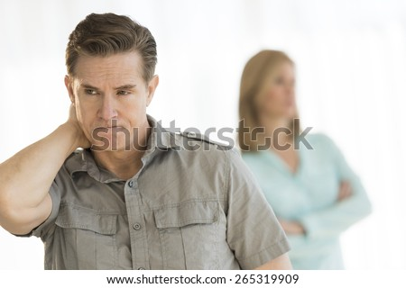 Angry mature man looking away with woman standing in background at home - stock photo