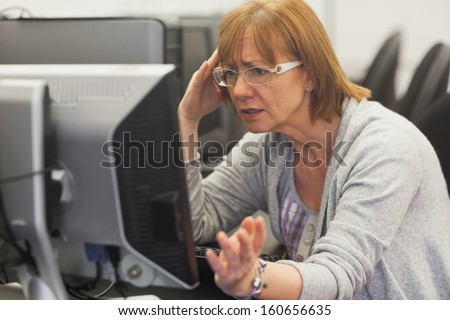 Angry mature student working with computer in computer class - stock photo