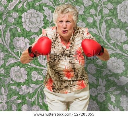 Angry Mature Woman Wearing Boxing Gloves Against Wallpaper - stock photo
