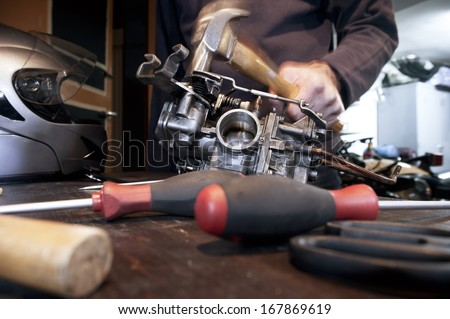 Angry mechanic with hammer trying to repair the carburetor of his motorcycle - stock photo