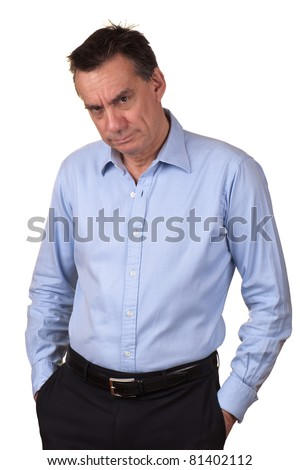 Angry Middle Age Man in Blue Shirt with Grumpy Expression and Hands in Pockets - stock photo