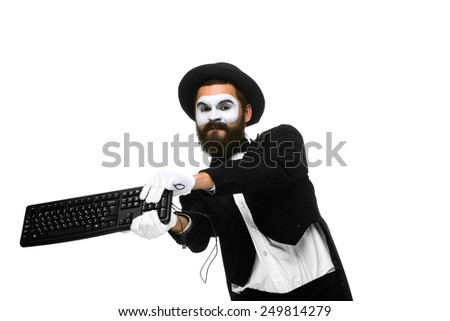 Angry mime as a businessman is destroying a keyboard. isolated on white background - stock photo