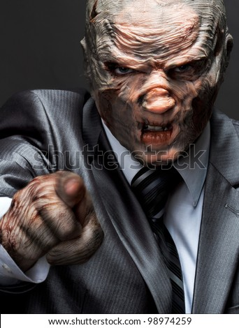 Angry monster in business suit pointing to you - stock photo